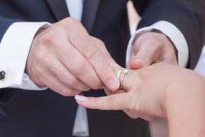 man places ring on womans finger during wedding ceremony